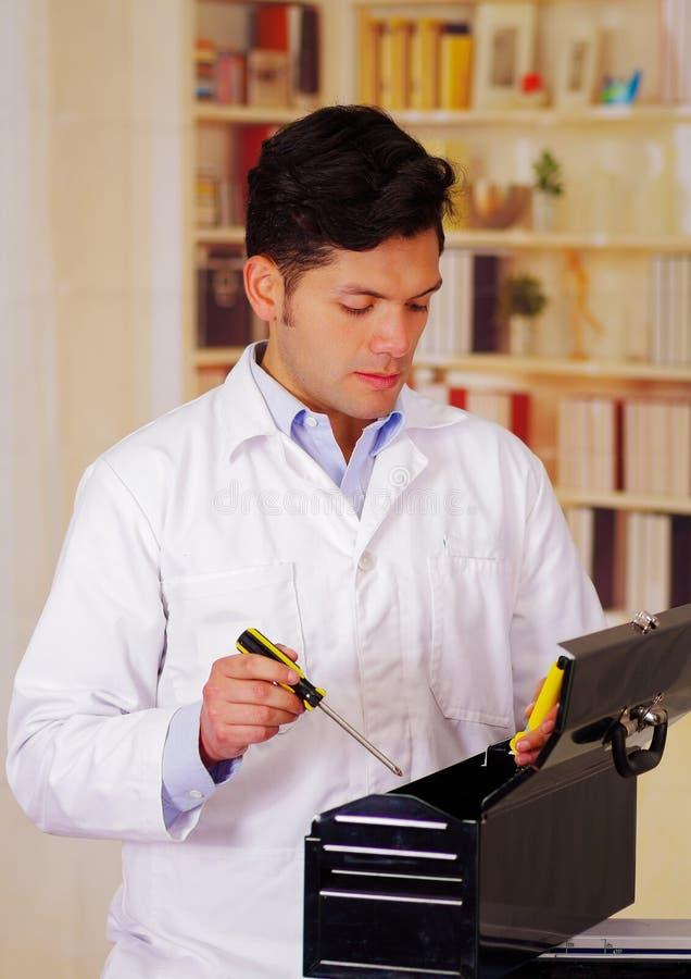 L'uomo laborioso apen una cassetta portautensili nera e la tenuta del cacciavite in sua mano immagine stock libera da diritti
