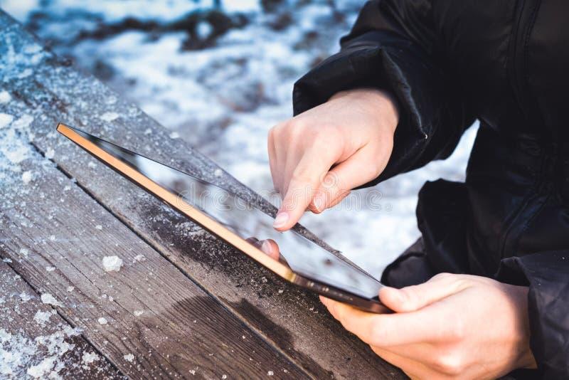 L'uomo lancia attraverso le foto sulla compressa mentre si siede ad una tavola di legno immagine stock libera da diritti