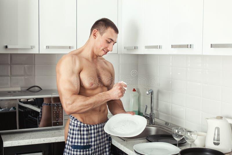 L'uomo lava un piatto immagini stock