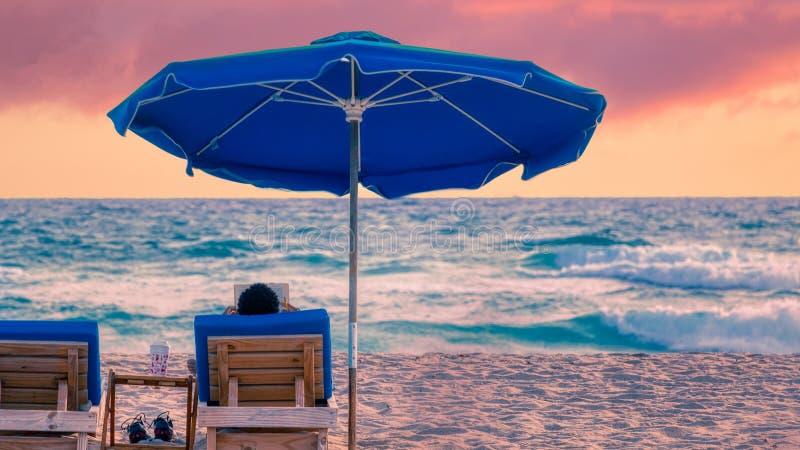 L'uomo legge il libro dall'oceano sulla spiaggia di Florida durante l'alba drammatica fotografie stock libere da diritti