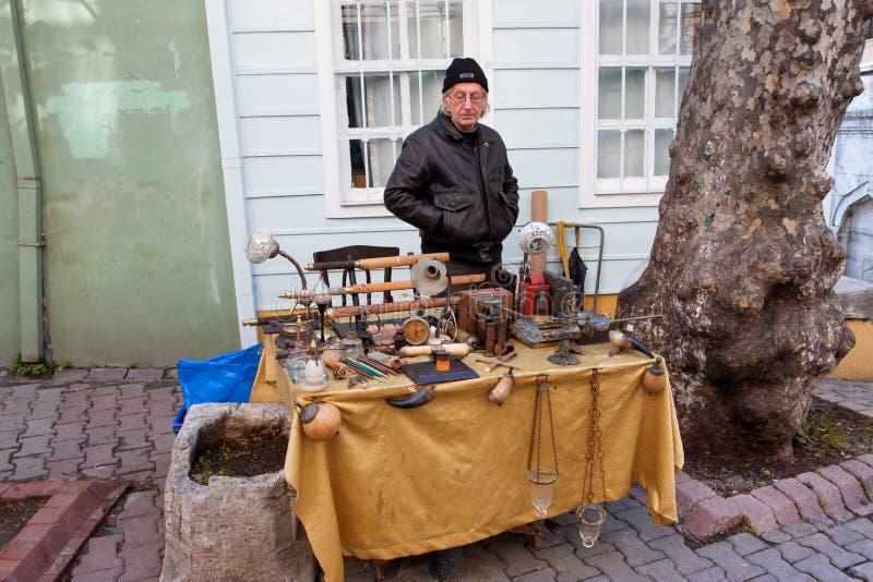 L'uomo maggiore vende gli oggetti d'antiquariato sul servizio di pulce immagini stock
