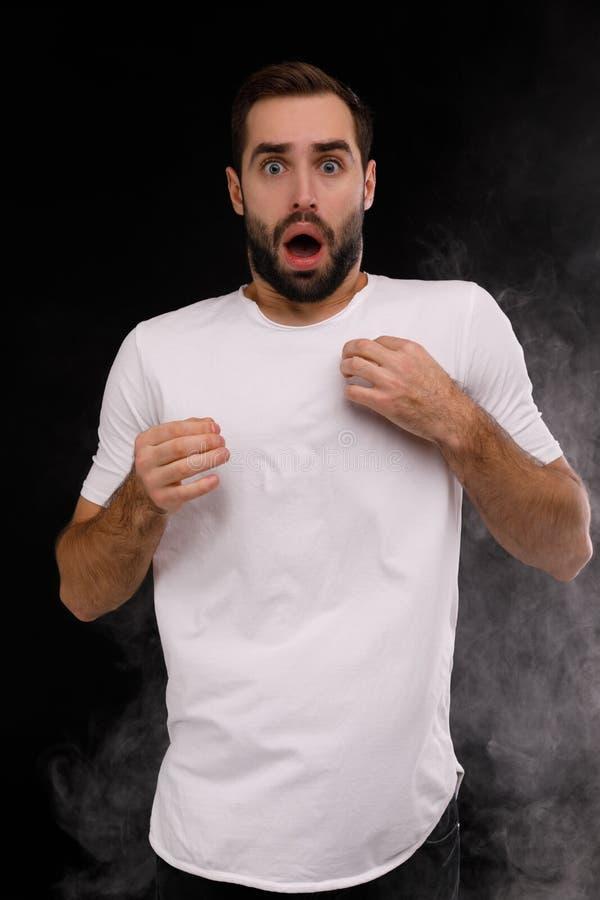 L'uomo in maglietta bianca odia il fumo della sigaretta fotografia stock