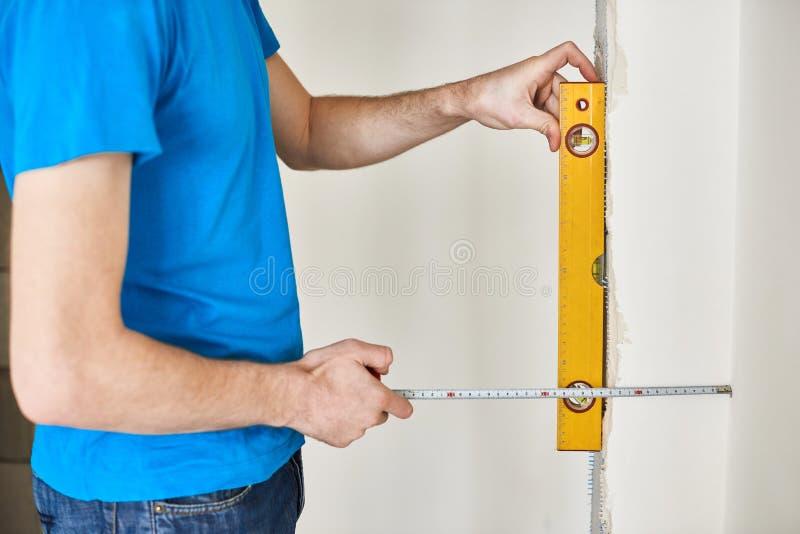 L'uomo in maglietta blu controlla il livello della parete fotografia stock libera da diritti