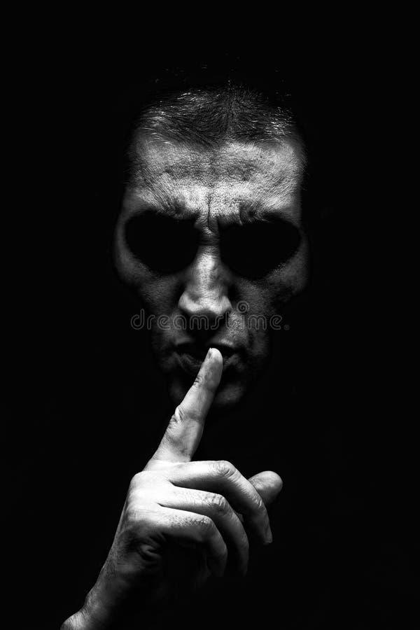 L'uomo maturo arrabbiato con un sembrare aggressivo che fa il silenzio firma dentro un modo minaccioso e terrificante fotografie stock