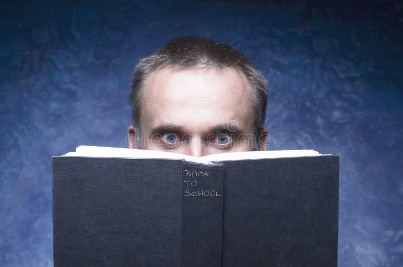 L'uomo maturo che è messo a fuoco ed agganciato dal libro, libro aperto di lettura, ha sorpreso il giovane, stupente osserva semb immagini stock