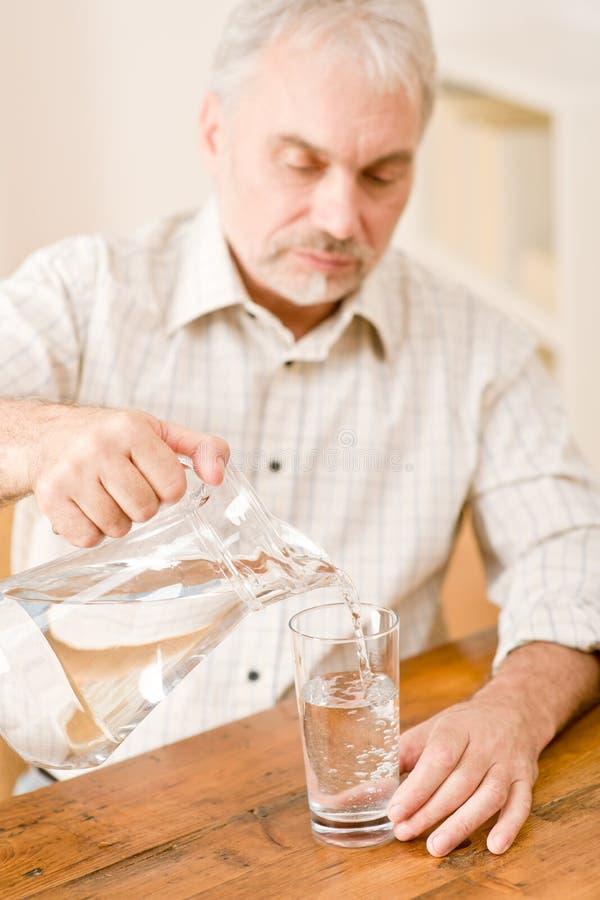 L'uomo maturo maggiore versa l'acqua che si siede alla tabella fotografia stock libera da diritti