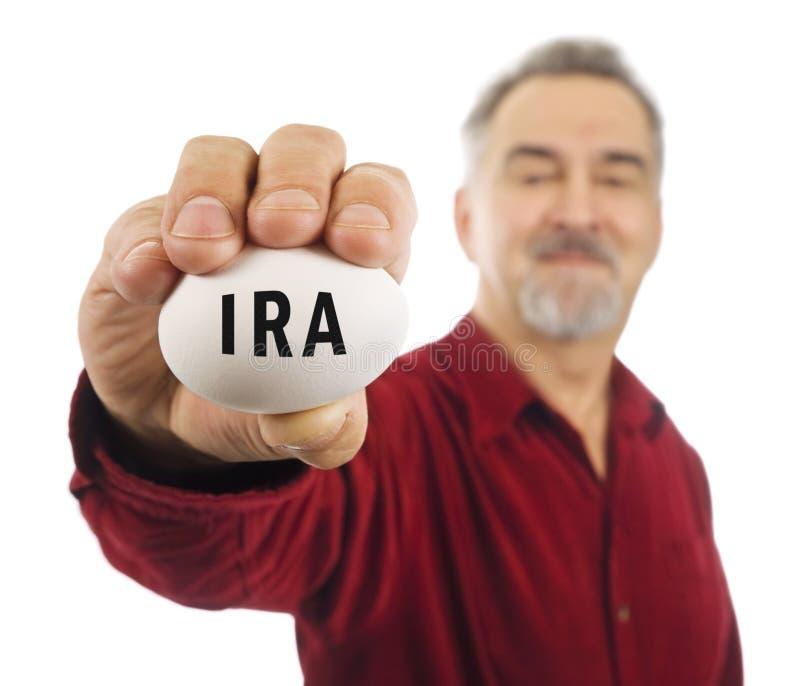 L'uomo maturo tiene l'uovo di nido bianco con l'IRA su esso. fotografia stock libera da diritti