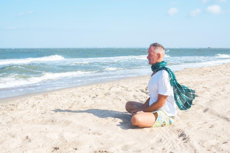 L'uomo medita su spiaggia fotografia stock libera da diritti