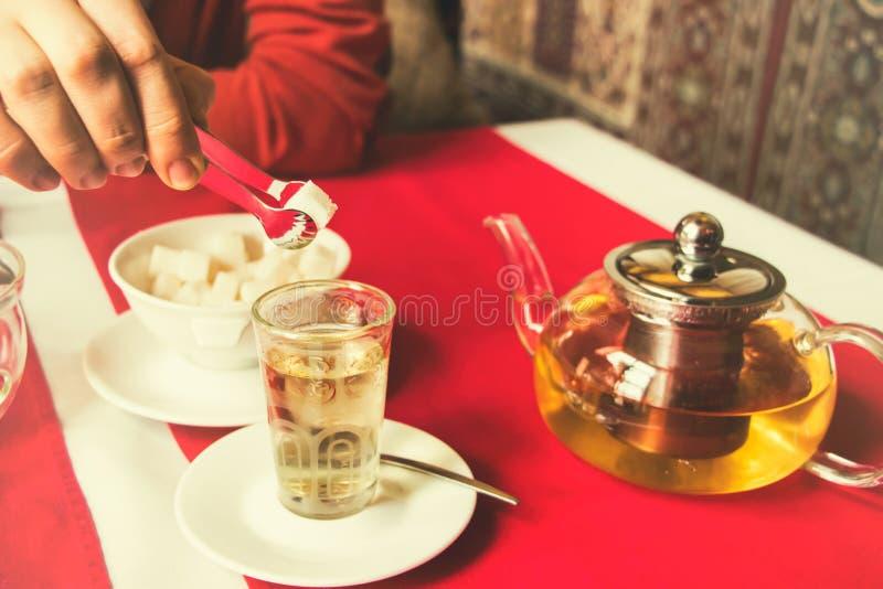 L'uomo mette lo zucchero in tè immagini stock
