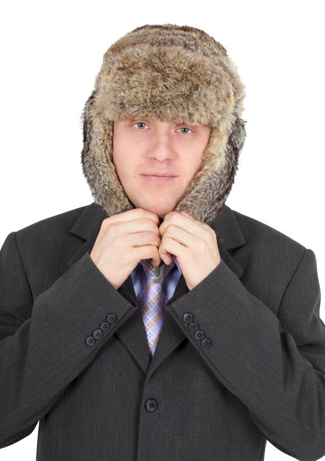 L'uomo mette sopra la testa un cappello di pelliccia immagine stock libera da diritti