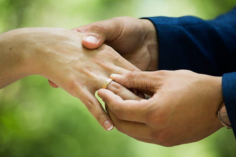 L'uomo mette un anello di fidanzamento su una donna immagini stock libere da diritti