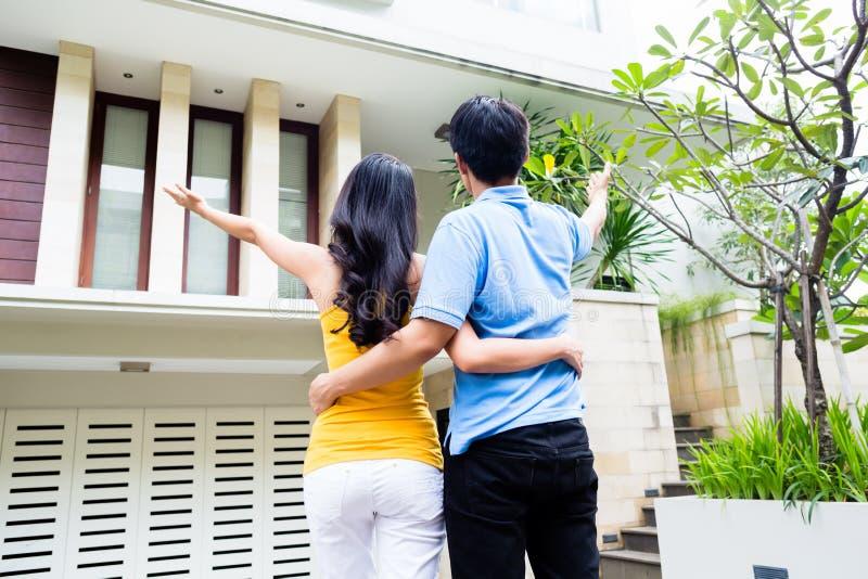 L'uomo mostra alla sua donna la loro nuova casa asiatica immagine stock