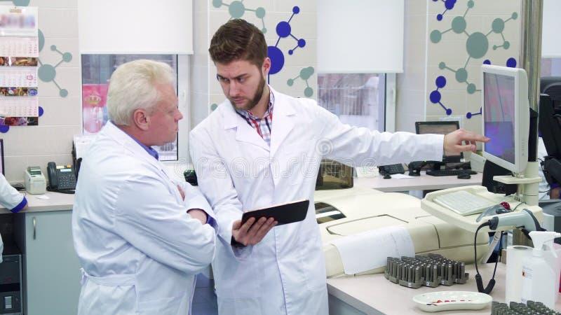 L'uomo mostra qualcosa sul monitor al suo collega al laboratorio fotografia stock libera da diritti