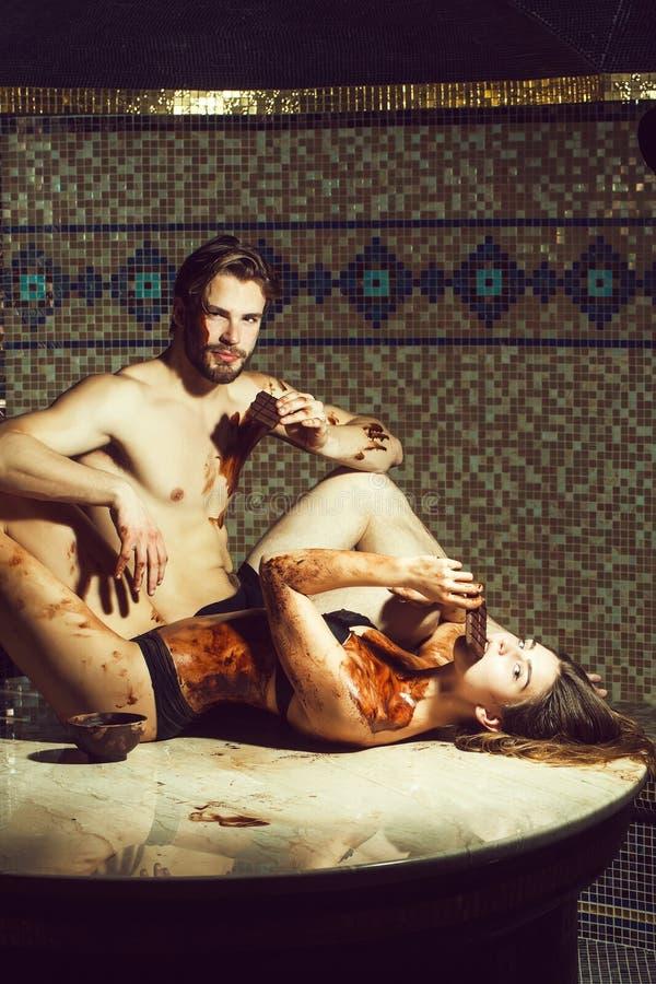 L'uomo muscolare e la donna sexy mangiano il cioccolato dopo il massaggio del salone fotografie stock libere da diritti