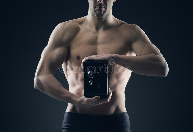 L'uomo muscolare protegge il risparmio fotografia stock libera da diritti