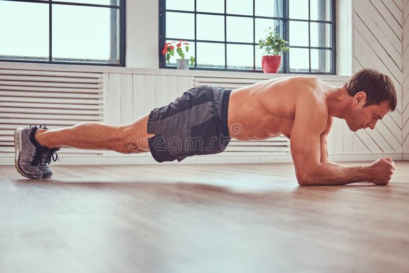 L'uomo muscolare senza camicia bello che fa l'esercizio della plancia sulle mani per il corpo scolpisce sul pavimento a casa fotografia stock libera da diritti