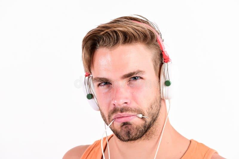 L'uomo muscolare sexy ascolta audio uomo in cuffie su bianco Libro elettronico libro audio d'ascolto dell'uomo non rasato stylish immagini stock