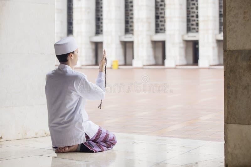 L'uomo musulmano devoto prega all'Allah immagine stock