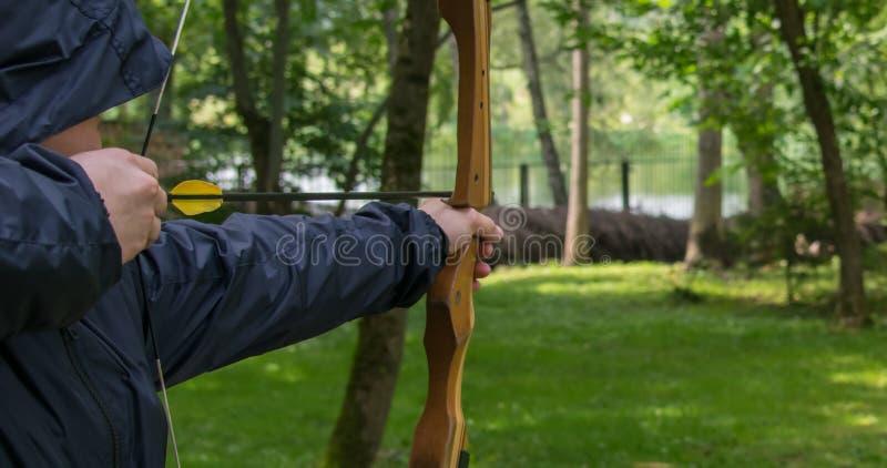 l'uomo nel cappuccio, tirato il bowstring, per un colpo ulteriore dall'arco nell'obiettivo immagini stock