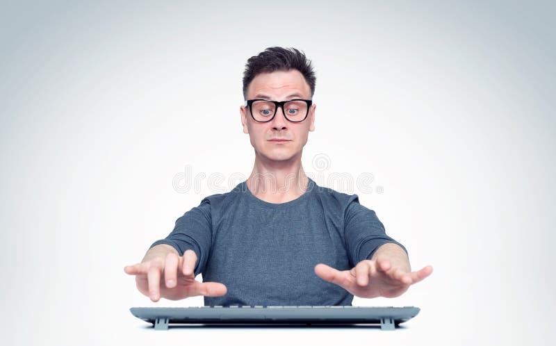 L'uomo nel funzionamento di vetro al computer, le sue mani sorvola la tastiera mentre scrive Front View fotografia stock