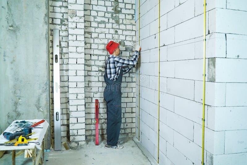 L'uomo nel lavoro indossa l'installazione delle rotaie del metallo sulla parete aerata del blocco in calcestruzzo immagine stock