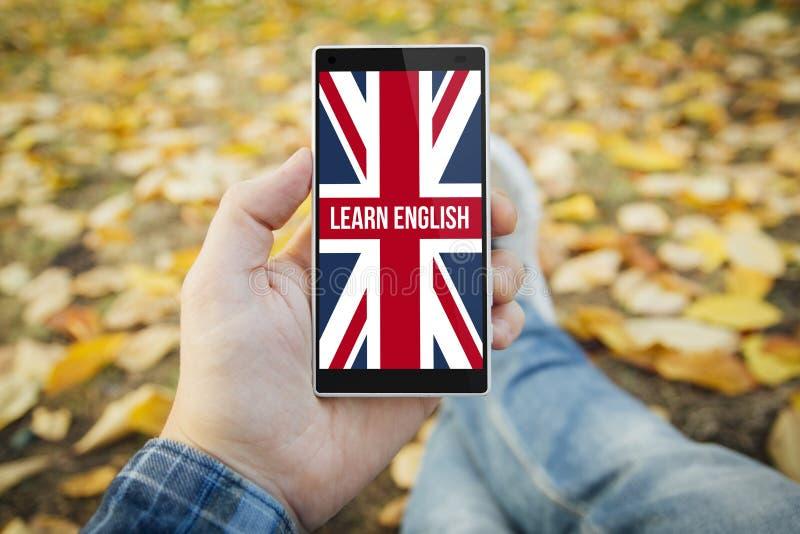 l'uomo nel parco impara lo smartphone inglese immagini stock