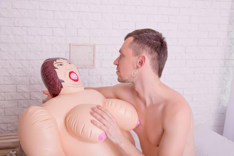 L'uomo nudo accarezza i seni di una bambola gonfiabile immagini stock