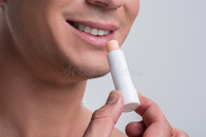 L'uomo nudo allegro sta usando il balsamo cosmetico immagine stock libera da diritti