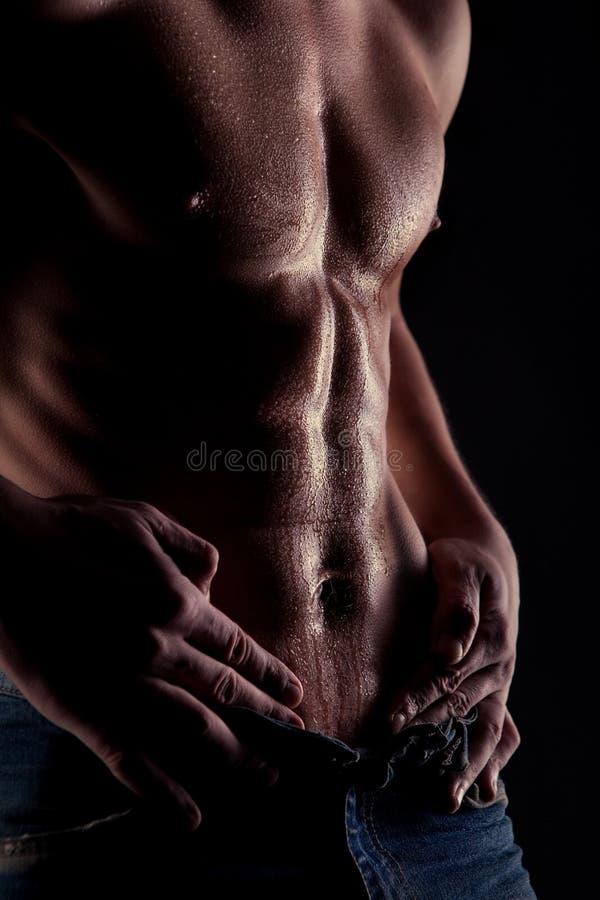 L'uomo nudo muscolare con acqua cade sullo stomaco fotografia stock libera da diritti