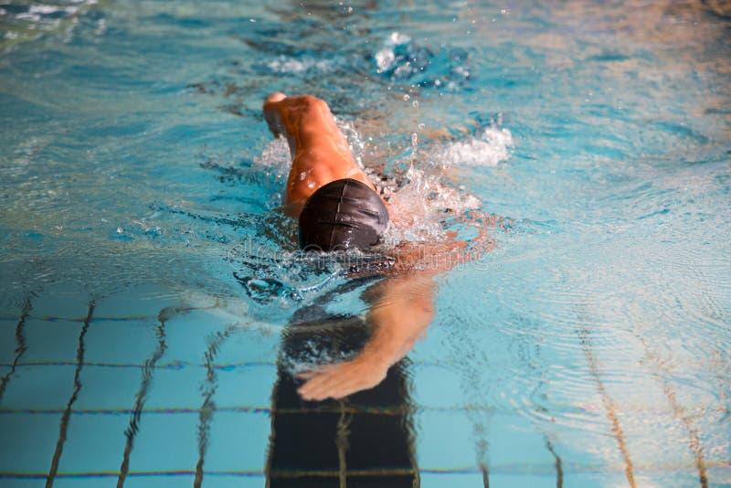 L'uomo nuota lo stile di movimento strisciante anteriore nella piscina fotografia stock