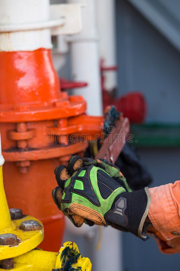 L'uomo o il marinaio capace sta aprendo la valvola di grande tubo Carico liquido fotografie stock libere da diritti