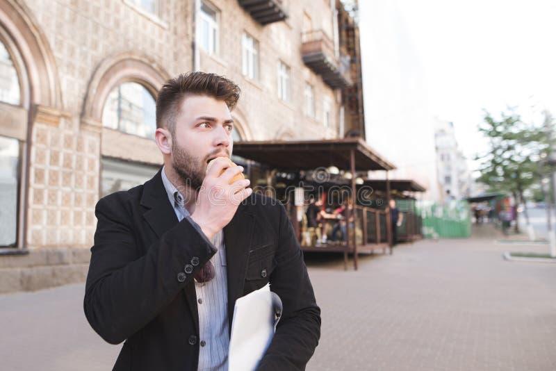 L'uomo occupato scende la via, mangia un panino e distoglie lo sguardo L'uomo di affari sta avendo un viaggio degli alimenti a ra fotografie stock