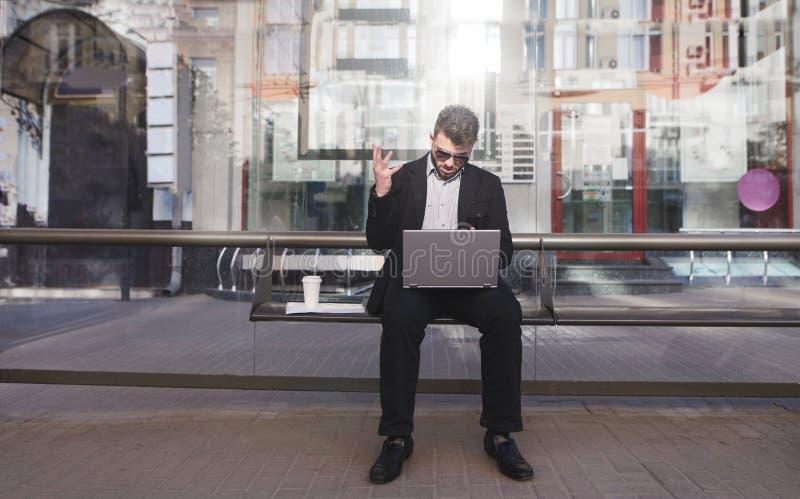 l'uomo occupato si siede su una fermata e sugli impianti di transito pubblico su un computer portatile Lavoro sul modo all'uffici immagine stock