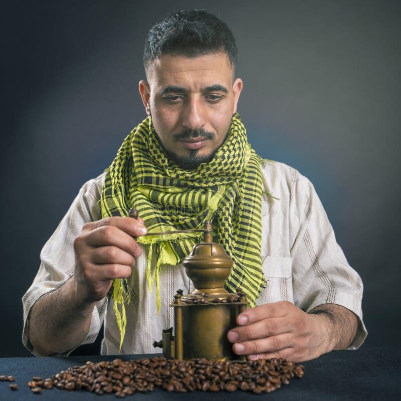 L'uomo orientale in vestito arabo nazionale tradizionale, frantuma i chicchi di caffè in un macinacaffè di rame anziano immagine stock