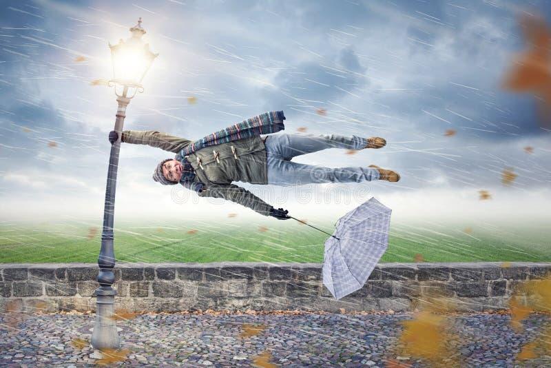 L'uomo ottiene soffiato via da una tempesta fotografie stock libere da diritti