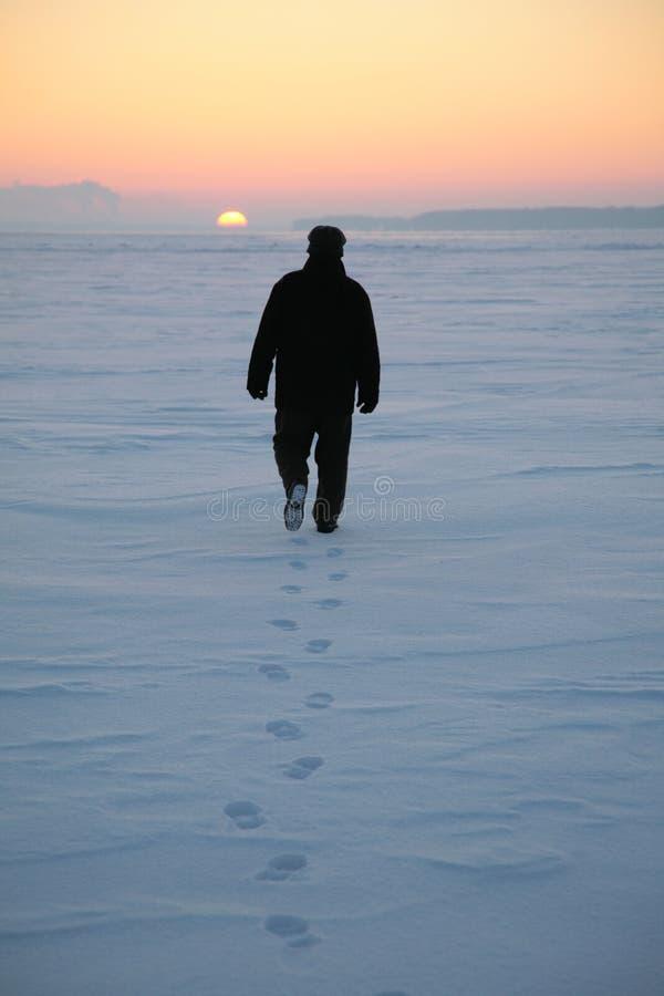 L'uomo passa attraverso il campo nevoso 2 fotografia stock libera da diritti