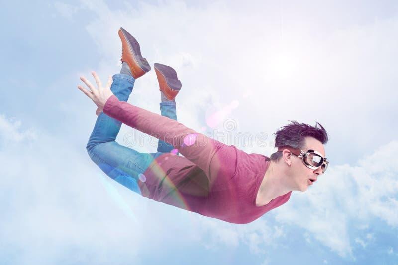 L'uomo pazzo negli occhiali di protezione sta volando dentro nel cielo nuvoloso Concetto del saltatore fotografia stock