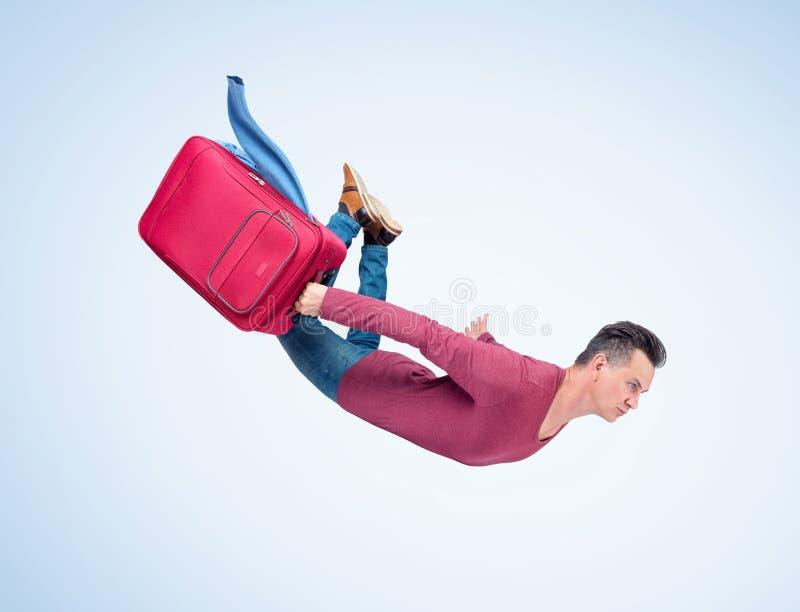 L'uomo pazzo vola nel cielo con una valigia rossa con i vestiti blu d'ondeggiamento Il concetto è più veloce sulla vacanza immagine stock