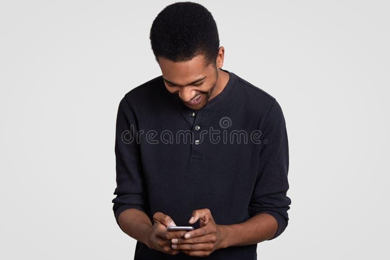 L'uomo pelato scuro estatico con taglio di capelli di afro, risate felicemente, tiene il telefono cellulare, legge la storia dive fotografia stock