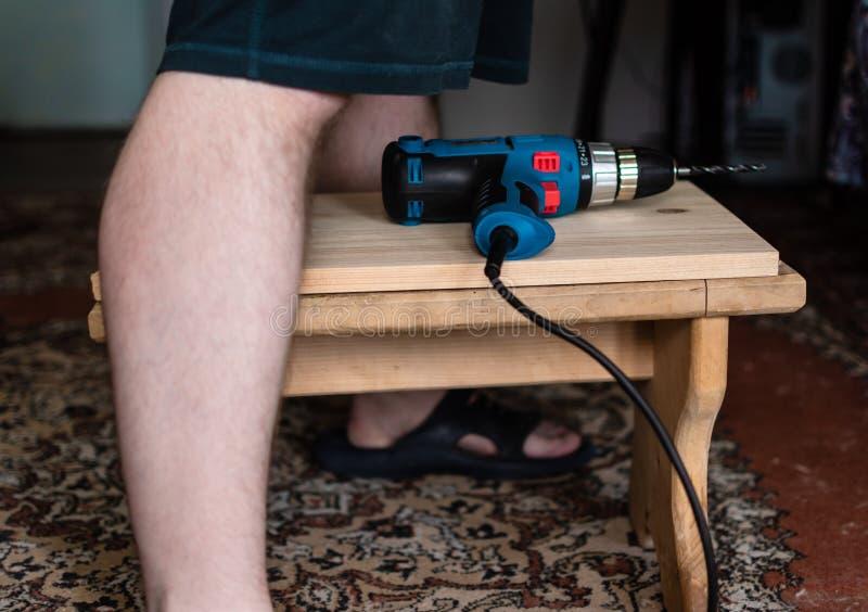 L'uomo perfora il bordo di legno delle gambe degli uomini fotografia stock