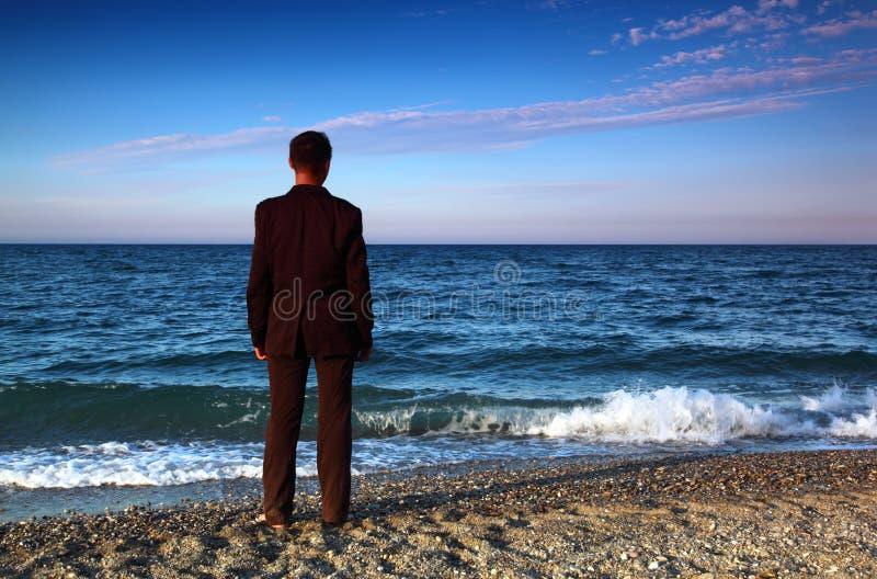 L'uomo a piedi nudi in vestito si leva in piedi indietro sul litorale di pietra immagine stock