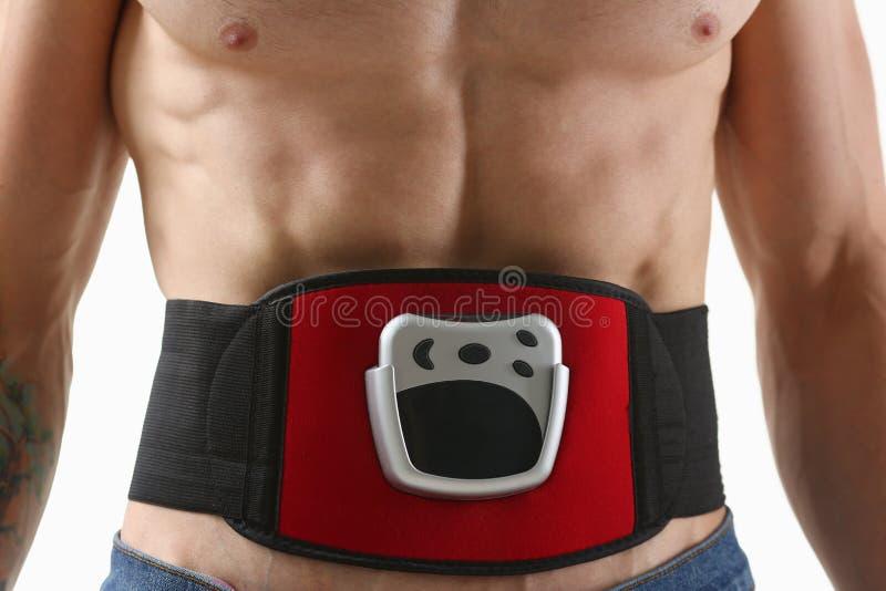 L'uomo piegato atletico utilizza un simulatore elettrico della cinghia per la formazione della stampa fotografia stock
