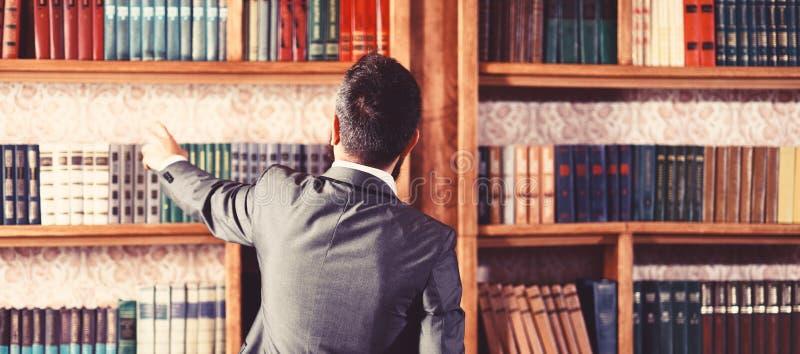 L'uomo prende il libro dallo scaffale Lo studente sta in biblioteca e sceglie il libro Il tipo in vestito astuto legge vicino all immagini stock libere da diritti