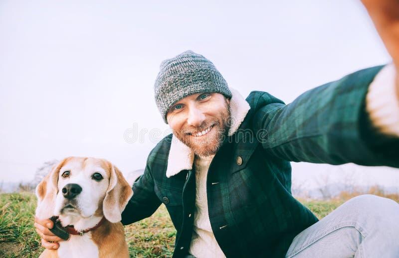 L'uomo prende la foto del selfie con il suo cane del cane da lepre del migliore amico fotografia stock