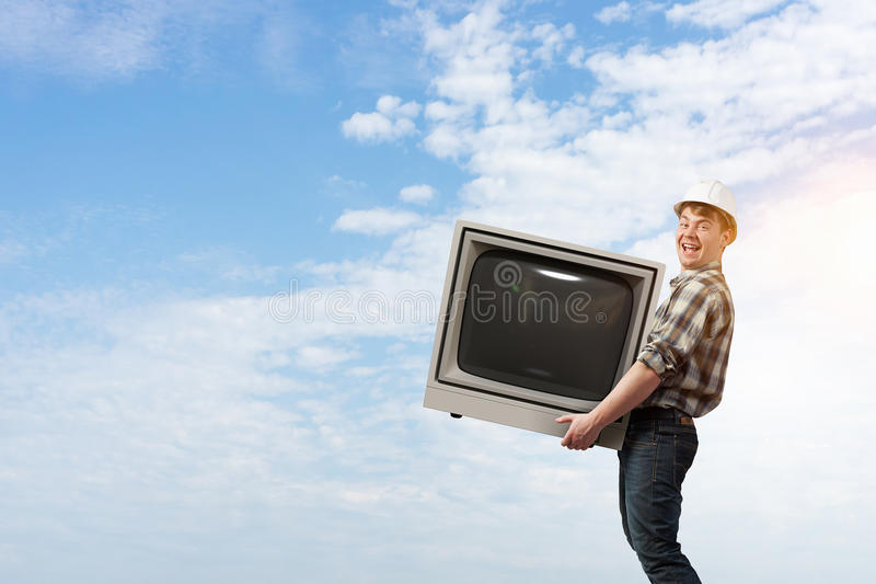 L'uomo prende la TV a servizio Media misti immagine stock