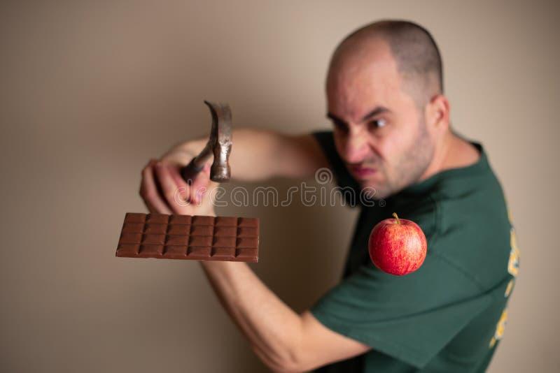 L'uomo prende un martello per fracassare una barra di cioccolato con una mano e per tenere una mela con l'altra immagini stock