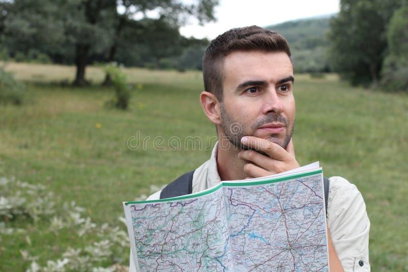 L'uomo preoccupato ha perso l'escursione sconcertante esaminando la mappa immagine stock