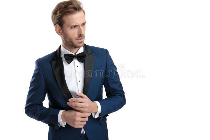 L'uomo preoccupato in vestito blu distoglie lo sguardo insieme con le mani immagine stock