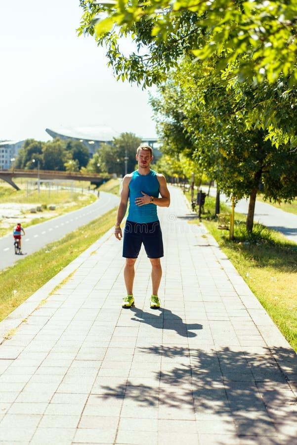 L'uomo prepara ad correre su una pista in un giorno soleggiato fotografia stock libera da diritti