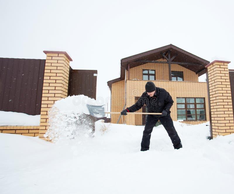 L'uomo pulisce la neve intorno alla casa fotografie stock